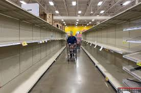 The store is filled with empty shelves and limited supplies left. Shopper is reaching to grab what she can. Photo courtesy of USA Today.
