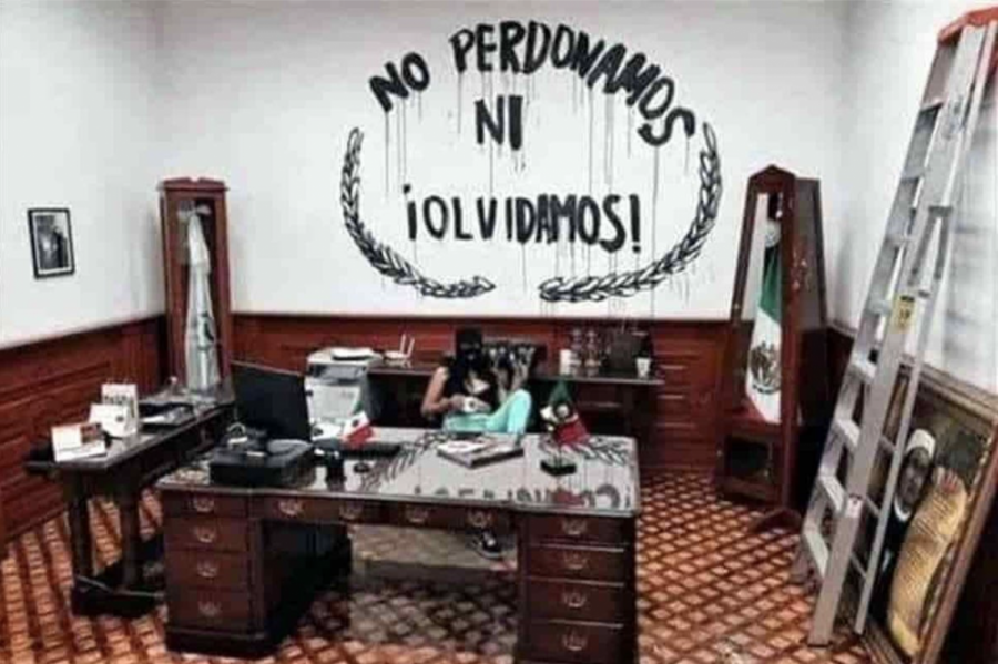 "One of the women that took over the National Human Rights Commission posing with the vandalized office. In the background the phrase painted to the wall which translates to ""We don't forgive, nor forget."""